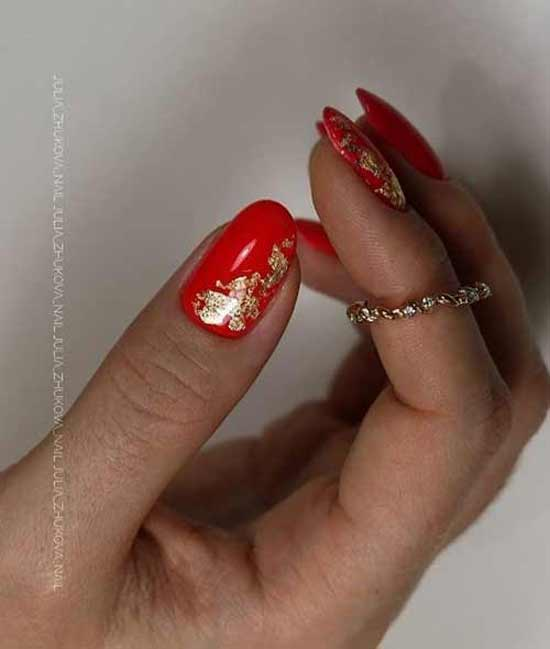 Red manicure with gold leaf