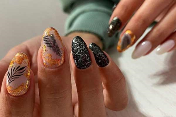 Stylish black manicure with sparkles in the photo