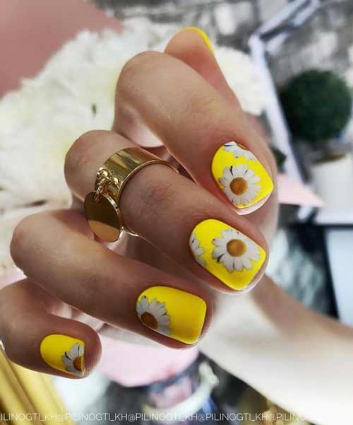 Yellow manicure with daisies